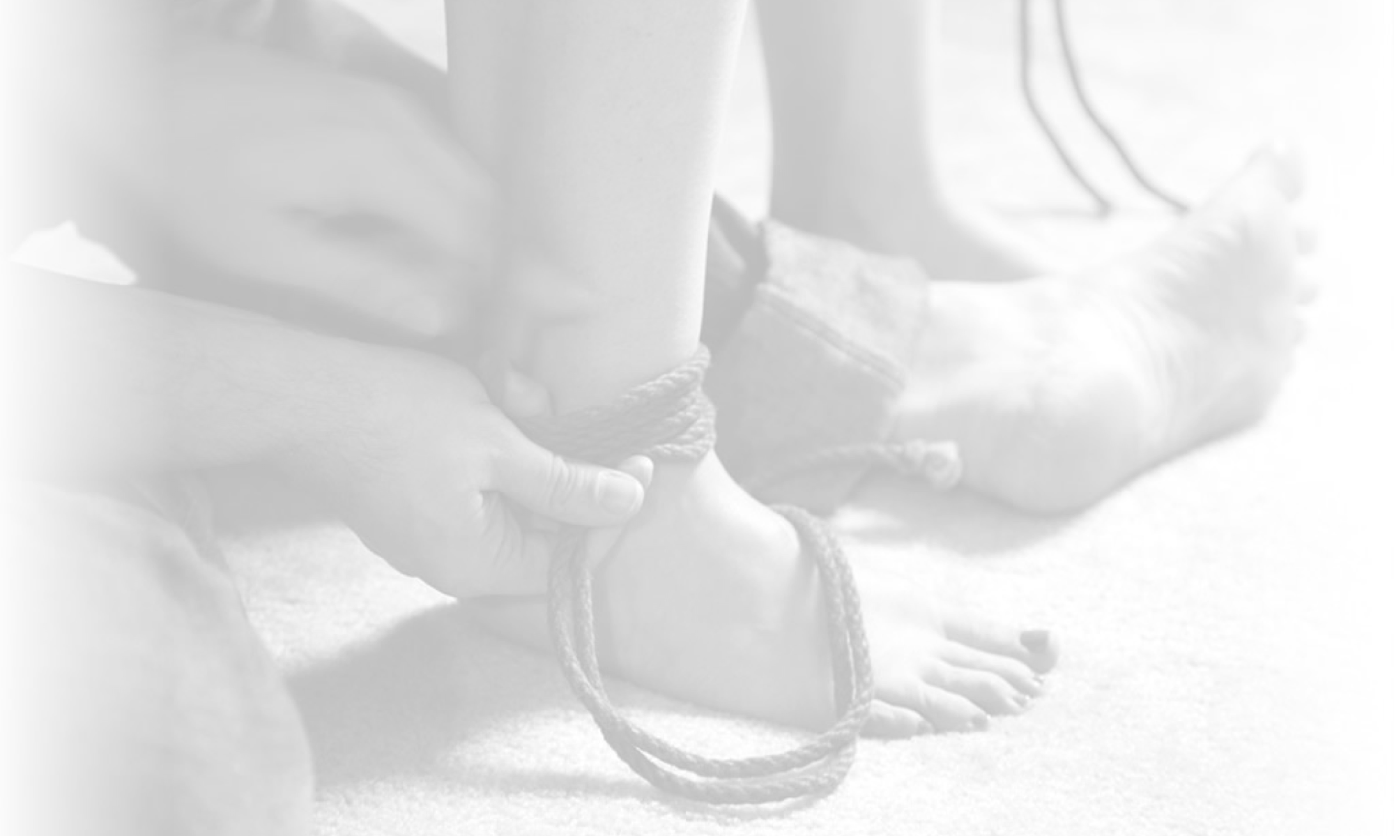 Image of feet with ankle being tied in a rope by male hands