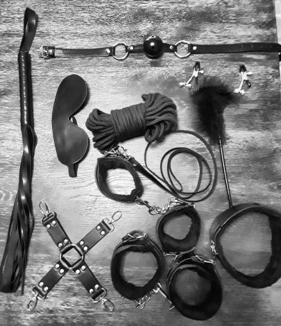 Array of bondage toys including: flogger, nipple clamps, ankle cuffs, wrist cuffs, collar, flogger, leash, ball gag, feather tickler