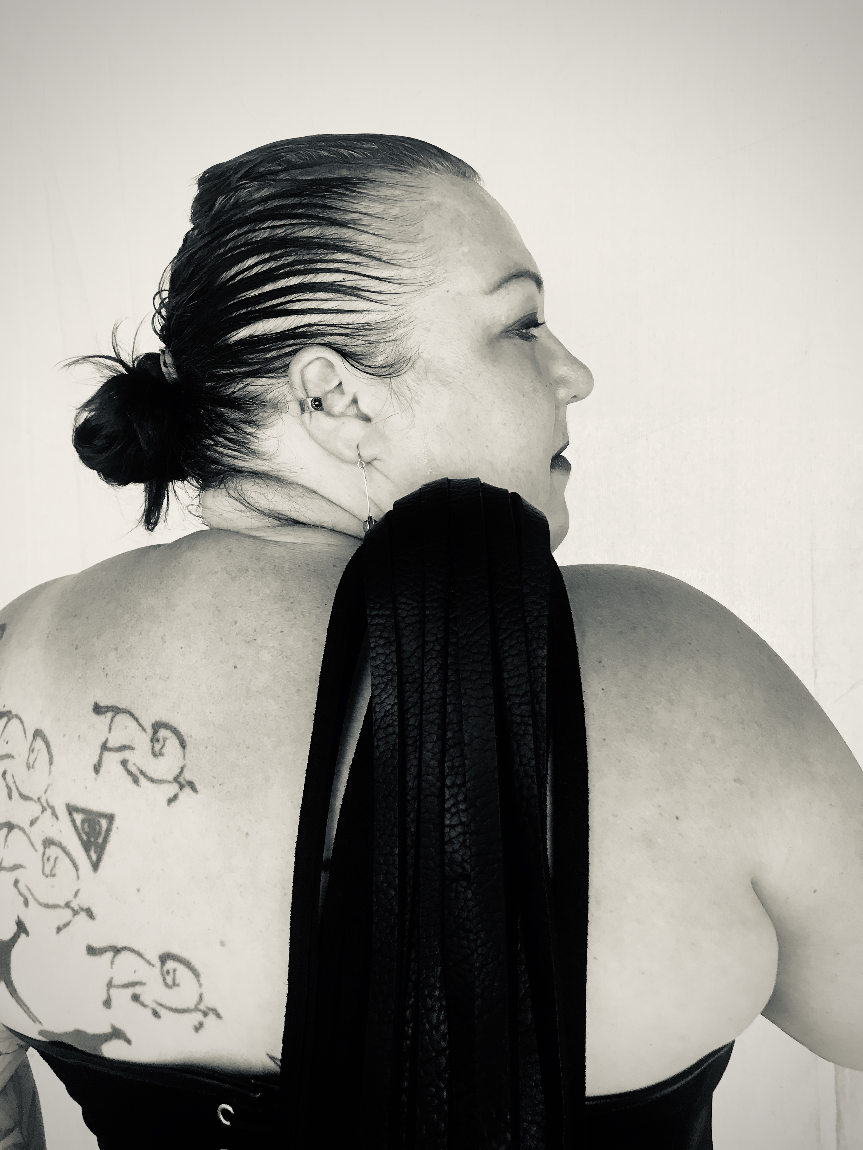 Back of white woman with tattoos holding a flogger